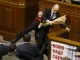 Rada deputy Oleg Barna removes Ukrainian Prime Minister Arseny Yatseniuk from the tribune, after presenting him a bouquet of roses, during the parliament session in Kiev, Ukraine, in this file picture taken December 11, 2015. REUTERS/Valentyn Ogirenko/Files      TPX IMAGES OF THE DAY